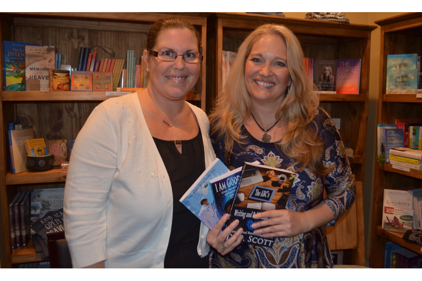 Author D.D. Scott, Sarasota, and Cheri Christiansen, owner of Four Pillars, hold a number of Scott'    s published books during her first writing workshop.