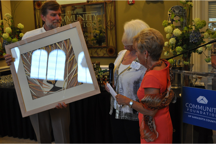Jack Donoghue and Marlene Hauck present a David Peterson work of art to Bunny Skirboll.