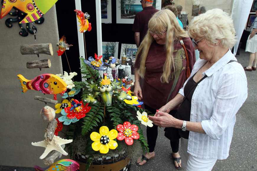 Nancy Koci and Esther Erickson look at some of the yard art creations by Aart Vark Studios during the 17th annual Siesta Key Craft Festival Saturday, Feb. 5, in Siesta Key Village.