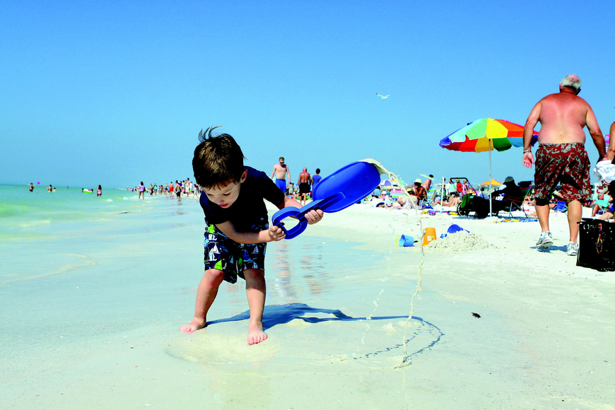 Brenden Bieth, 4, has fun digging in the sand with a big shovel while visiting Siesta Key Beach over Presidents Day weekend.