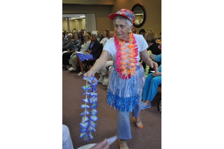 Surprise guest model and Longboat Observer reporter Dora Walters handed out Hawaiian leis as part of her beach-themed ensemble.