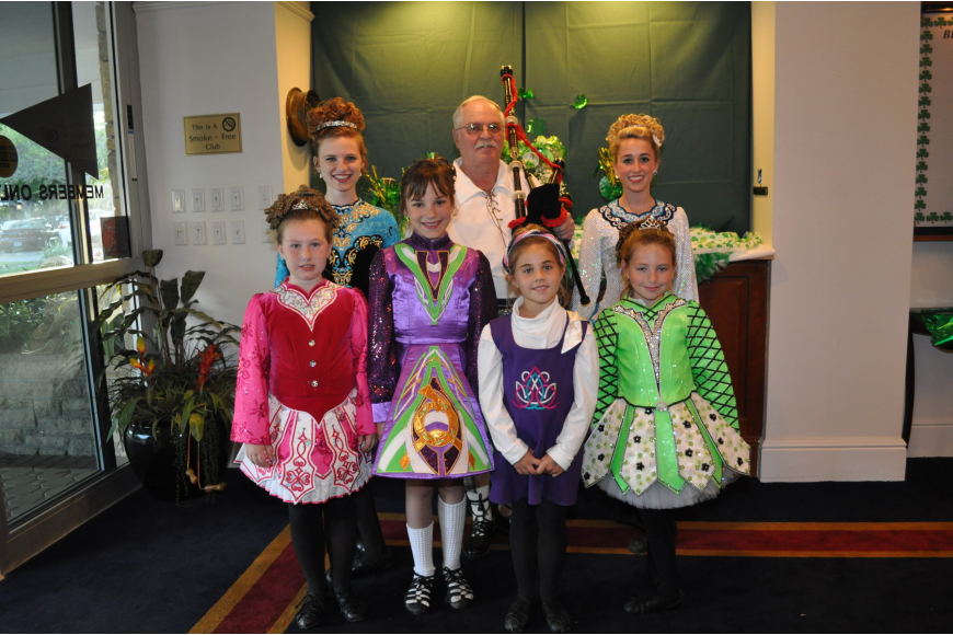 A group of adorable Irish dancers surrounds bagpiper Bill Buckley before he pipes them into the dining room for their St. Patrick's Day performance.