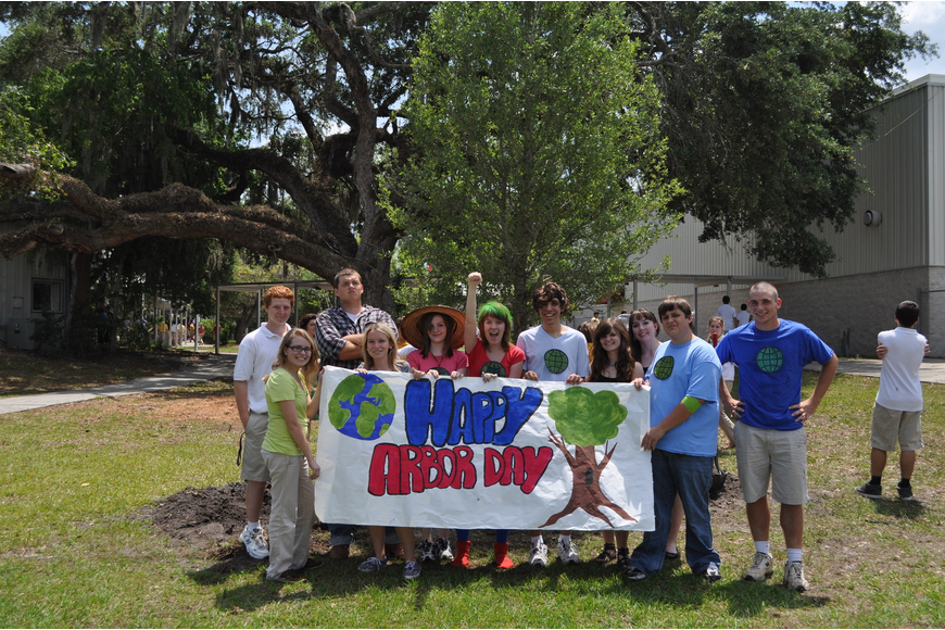 Cardinal Mooney students hold a banner they created for their Arbor Day celebration.