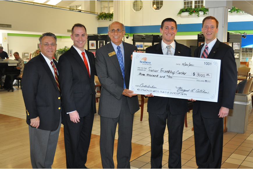 SunTrust Bank's Mike Lonas, Chris Tenaglia, Ryan Kern and Max Hannum present a $3,000 check to Senior Friendship Centers President and CEO Bob Carter.
