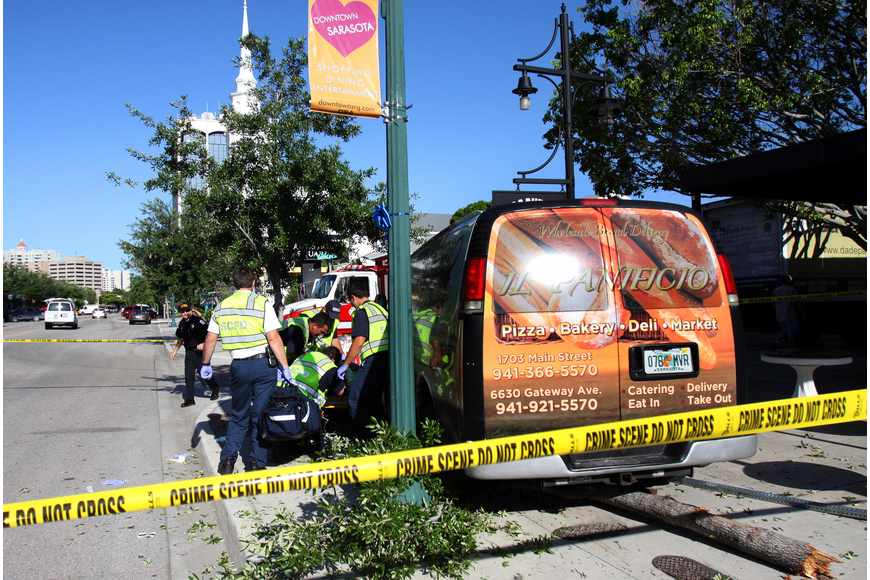 An Il Panifico van jumped the curb and hit a sign and tree before coming to a stop.