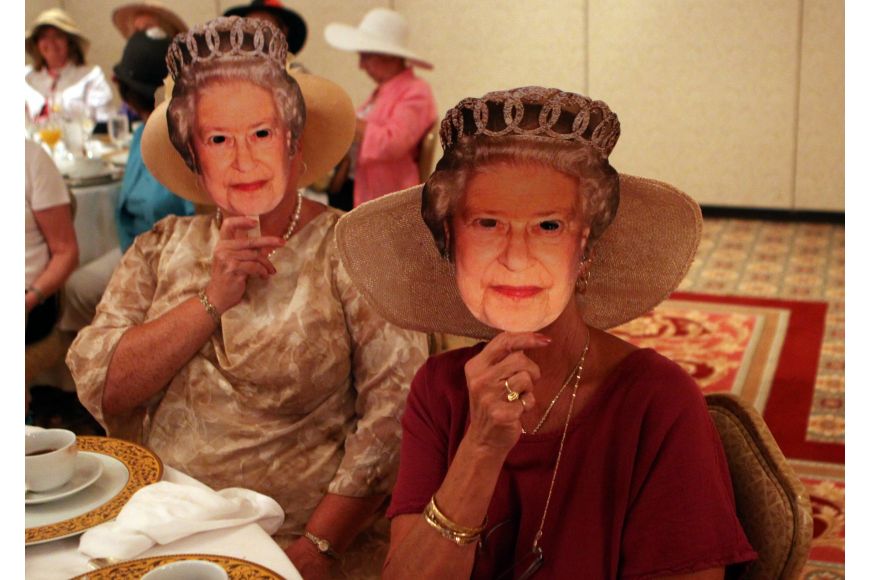 Angela Ward and Holly Kraft wear Queen Elizabeth cardboard masks Friday, April 29 while celebrating the royal wedding at the Ritz Carlton.