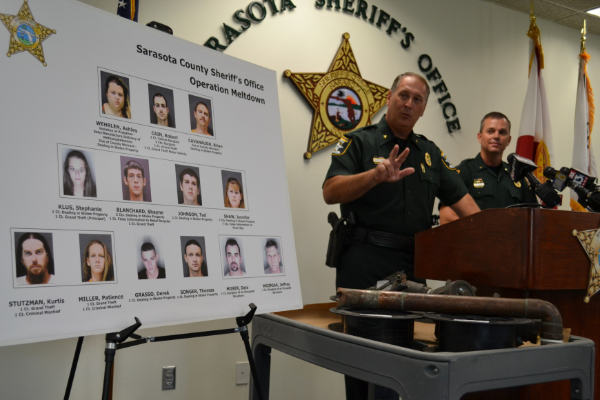 Sheriff Tom Knight, left, and Lt. John Jernigan display stolen metal and mug shots of the suspects in those thefts.