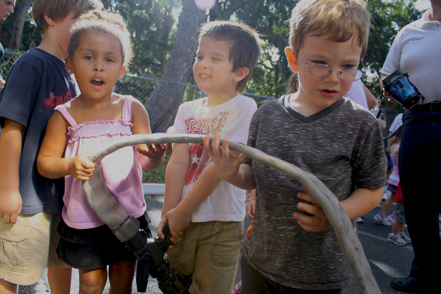 Francesca Magnotti, Liam Lizotte and Chance McArtor play with the fire hose.