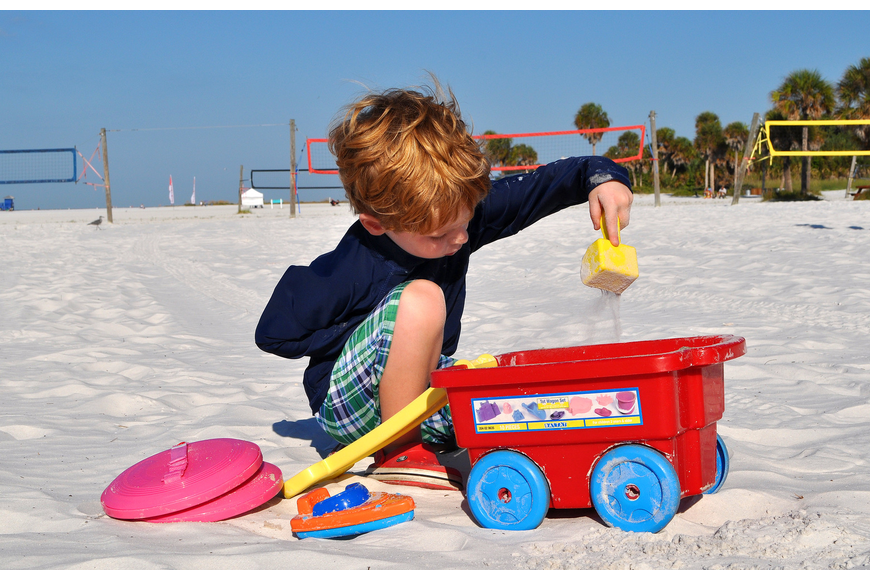 Patrick Fleming, 4, enjoys pouring sand in his little red wagon. Fleming is on vacation from Massachusetts along with his mother and father.