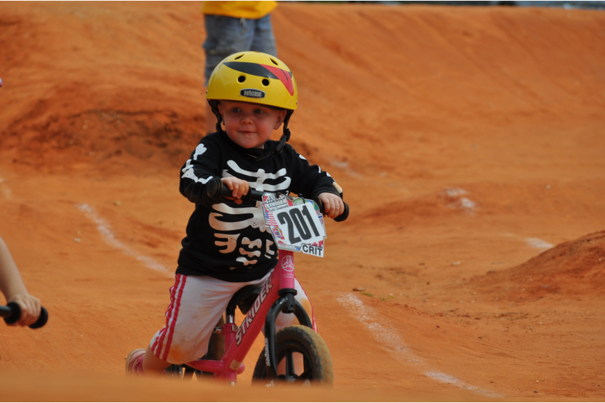 A toddler tests out a possible Halloween costume as she races around the track.