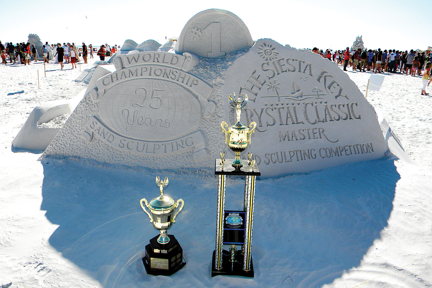 Trophies for the winners stand in front of the group carving of the event logos. Photos by Norman Schimmel