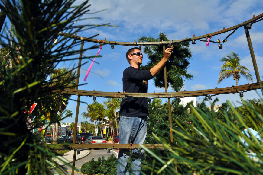 Alex Morel, of Wagner Realty, stands up on one of the rings of the tree to hang up a branch.