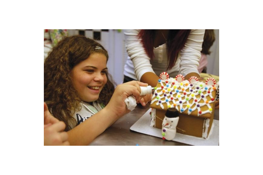 Mya Carter frosts the front of the Girls Inc. gingerbread house. Photo by Rachel S. O'Hara.