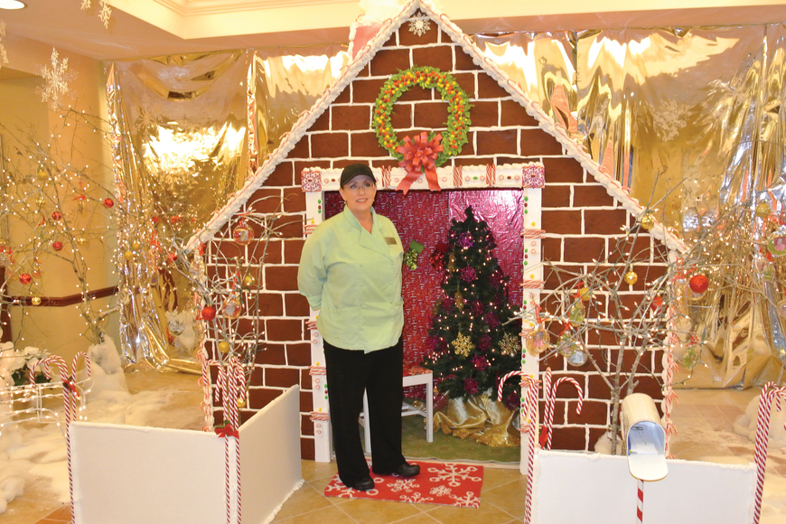 Deborah Kushlan stands in front of her 8-foot-tall gingerbread masterpiece. Photo by Loren Mayo.