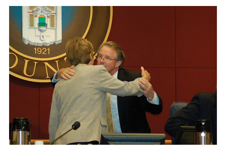 Before he walked away from the commission table mid-meeting May 25, Jim Ley shook hands and hugged all five county commissioners, including Chairwoman Nora Patterson. Photo by Robin Roy.