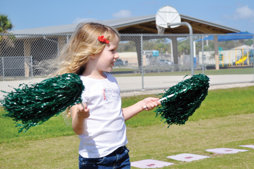 Cameron Seguin cheers on her big sister by waving pom-poms in the air at Tatum Ridge Elementary's March jog-a-thon.