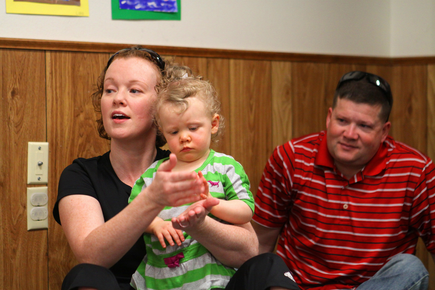 "Brian Moran watches as his wife, Erin, does the sign for ""cake"" and their daughter, Aura, 19 mos., tries to imitate."