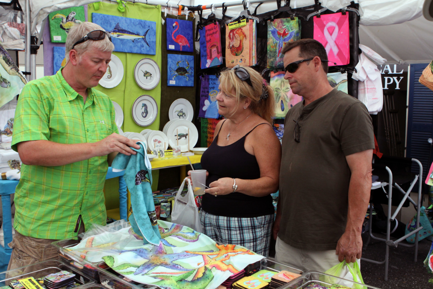 Denny Knight shows Jody and Walter Wiley some of his bright and fun fabrics inside his booth at Siesta Fiesta on Saturday.