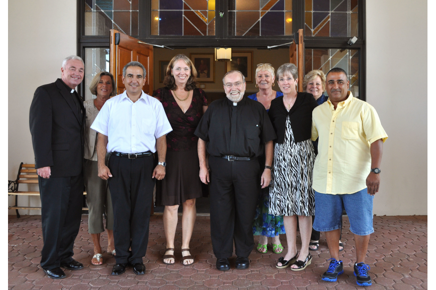 Msgr. Joseph Stearns poses with his staff including Deacon Kim Cohen, Arlene Luisa, Tony Garcia, Margaret Germain, Lynda Fischer, Diane Marcus, Donna Cohen and Ray Martinez, Sunday, May 20.