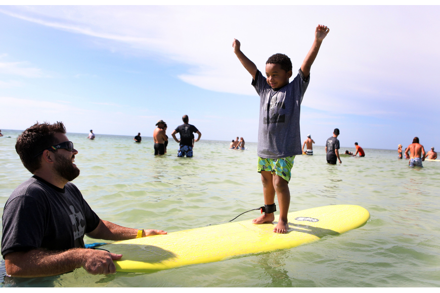 Mark Weeks laughs as Caiden Woodworth, 5, raises his arms up in the air victoriously Saturday, Sept. 15 during Hang 10 for Autism at Siesta Key Public Beach.