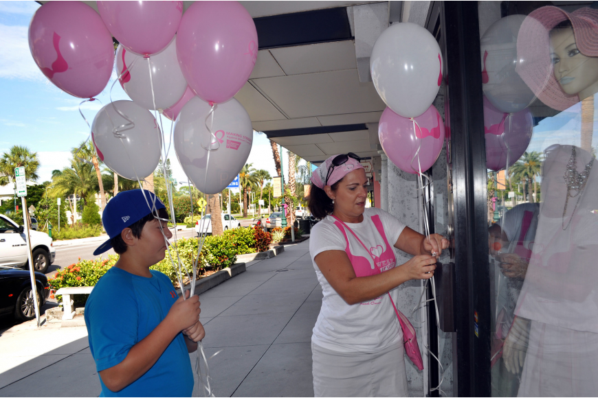 Michael Hampton, 11, helps his mom, Joanne, tie breast cancer awareness balloons onto the handles of stores that participated in the Circle Me Pink event Saturday, Oct. 6, on St. Armands Circle.