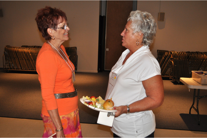 Kathy Roche and Karen Martin chit-chat with one another Monday, Oct. 8, during the welcome back luncheon for the Women's Guild at St. Michael the Archangel.