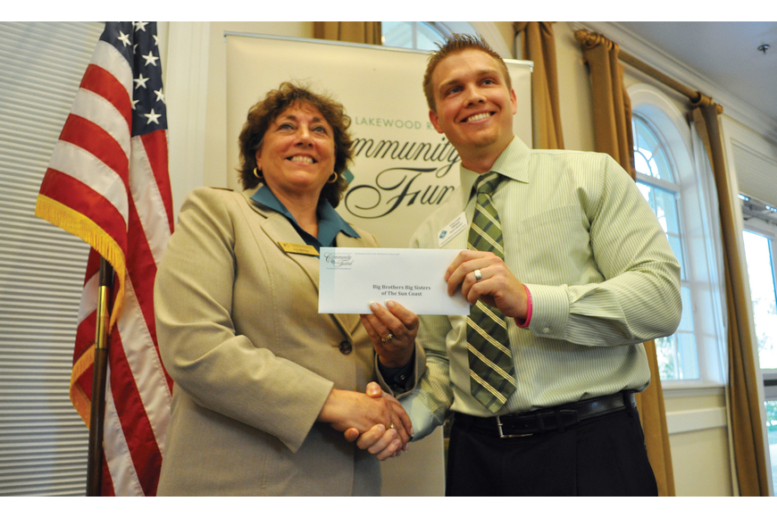 Joy Mahler, CEO for Big Brothers Big Sisters of the Sun Coast, accepts a check from Lakewood Ranch Community Fund Board Member Garrett Shinn, during a ceremony Oct. 19.