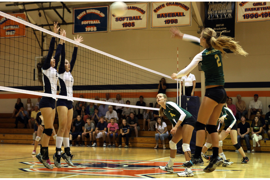 Melissa Johnson, No. 2, hits the ball over the net at Haley Preininger, No. 2, and Emily Greenwood, No. 7.