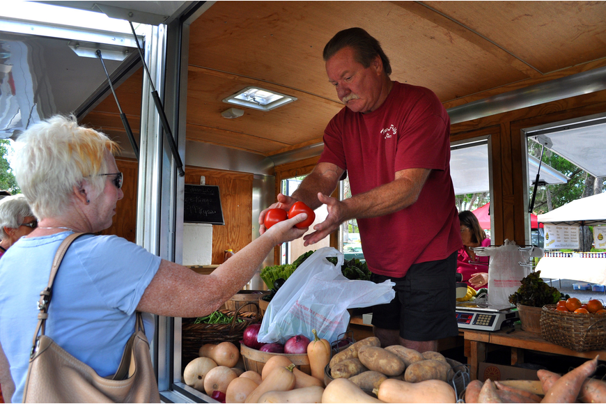 Julie Bales buys some green beans and tomatoes from Randy True from the True Family Farm trailer Sunday, Oct. 28, during the Fall Festival at the Centre Shops.