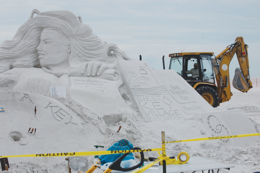Sand sculptors begin crafting the sponsor scroll for the Siesta key Crystal Classic Master Sand Sculpting Competition.