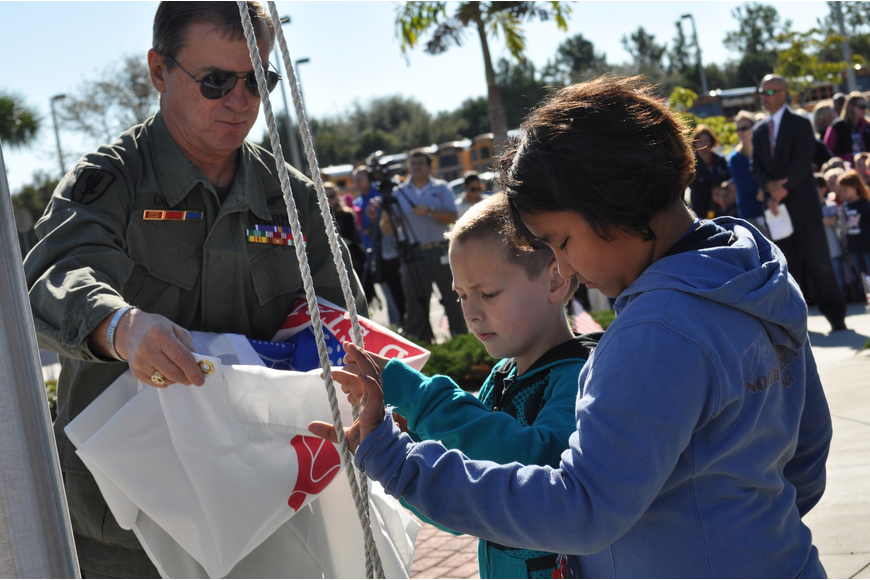U.S. Army veteran  Billy Coffey assists students at Freedom Elementary School as they raise the Army's flag during a Veteran's Day ceremony today.