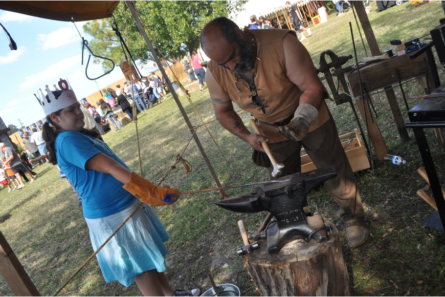 Abagael Burns waits for Blacksmith Pat DiPietro to make her a trinket.