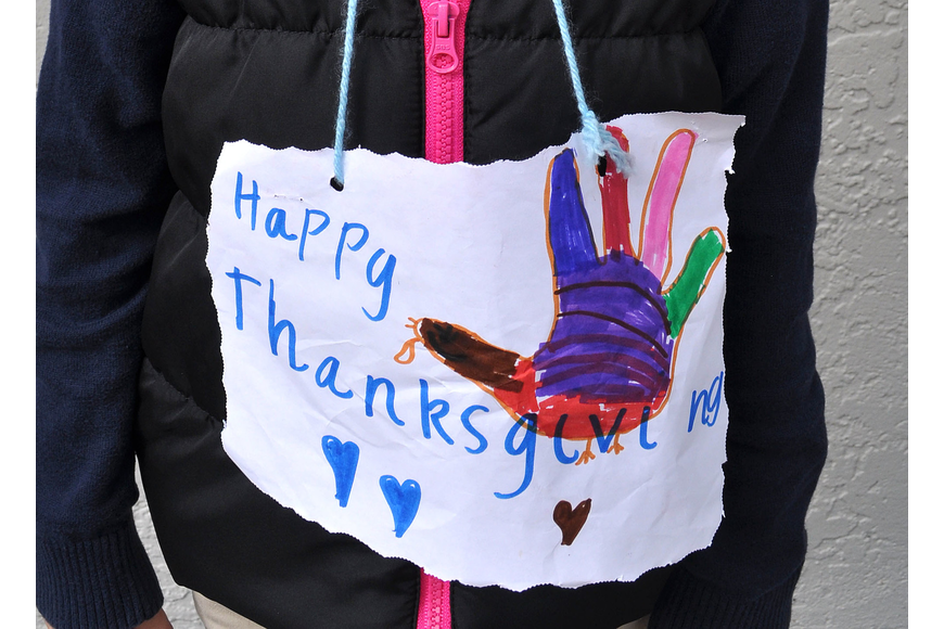 "Kristina Spilkova, 6, wore a handmade ""Happy Thanksgiving"" sign around her neck Tuesday, Nov. 20, during school at Out-of-Door Academy."