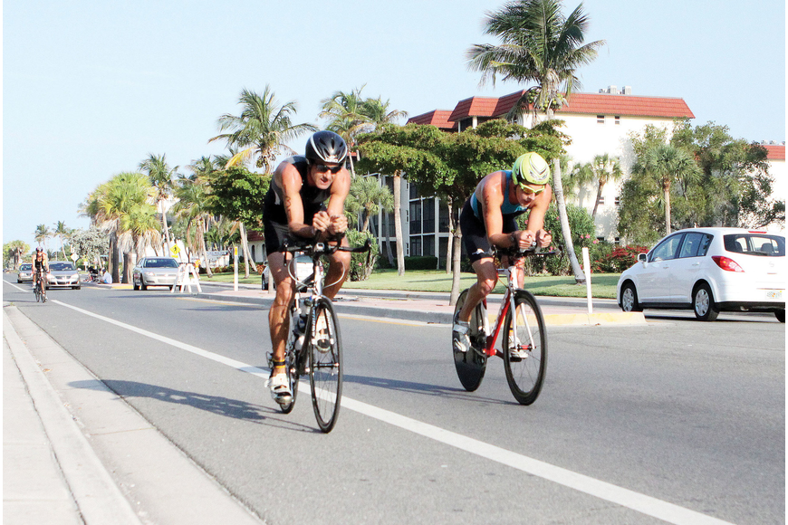 Bryan Prushinski, 43, and Eric hogenboom, 21, both of St. Petersburg, were neck and neck during the biking portion of the Florida International Triathlon, May 12, on Siesta Key.