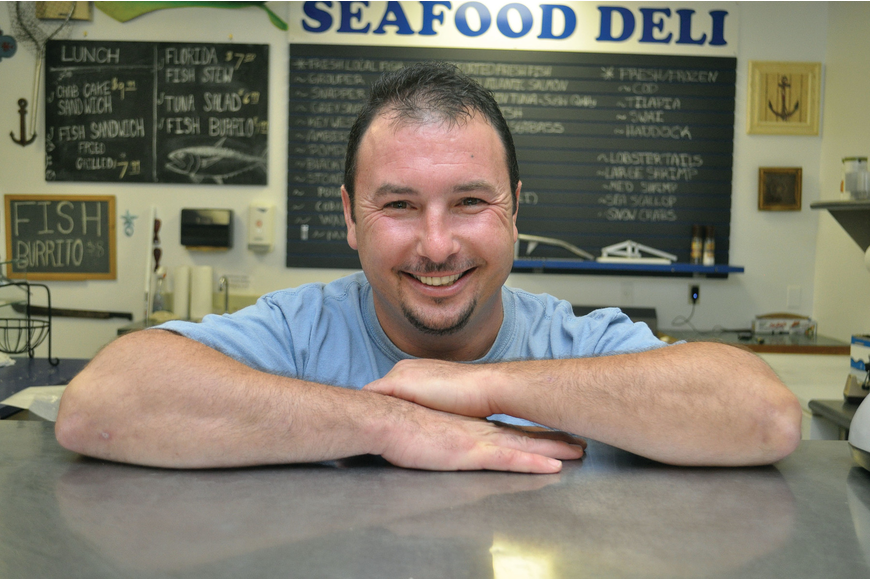 Scott Dolan, owner of Big Water Fish Market, stands behind the counter at his six-month-old store. During the recent tourist season, he shelled out 65 pounds of fish per day.