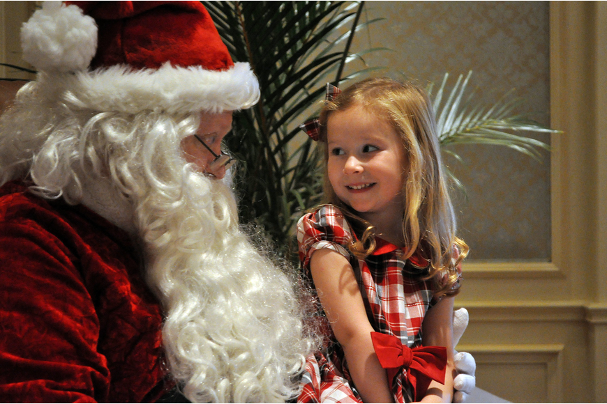 Norah Meyer, 3, smiles at Santa as he talks to her about what she might like for Christmas Sunday, Dec. 16, during the Breakfast with Santa event at the Ritz Carlton.