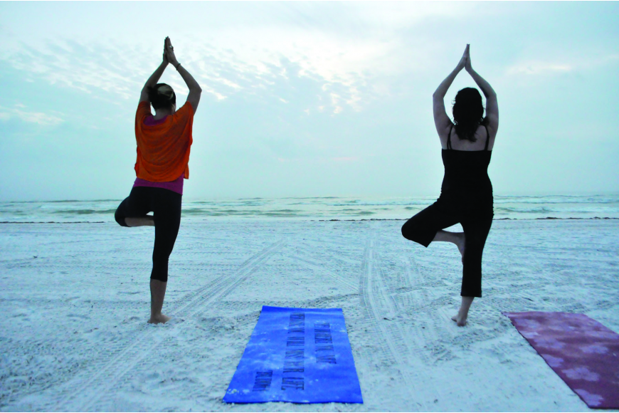 Courtney Kees leads Tabatha Giddens through a yoga class. Kees holds her sunset classes by the yellow lifeguard stand.