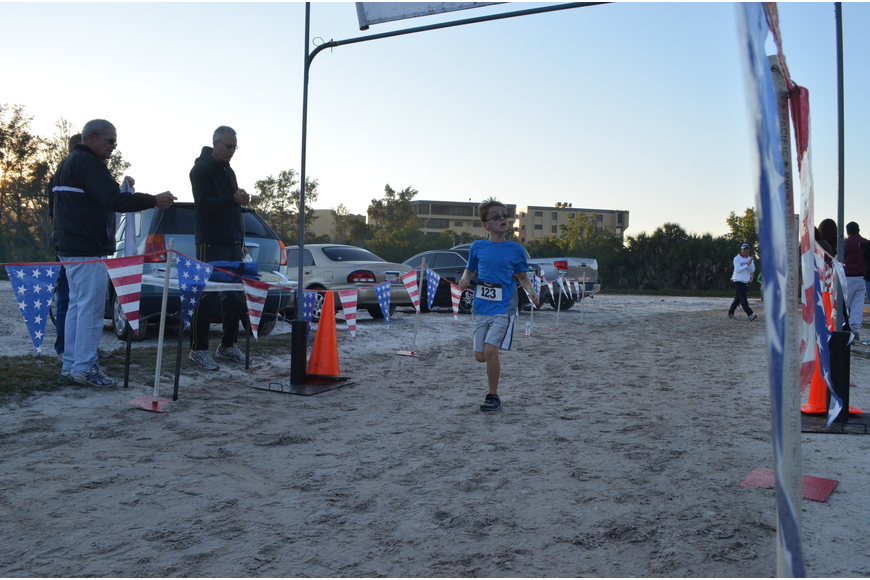 Camden Woznak, 8, checks his time as he runs into the finish line.