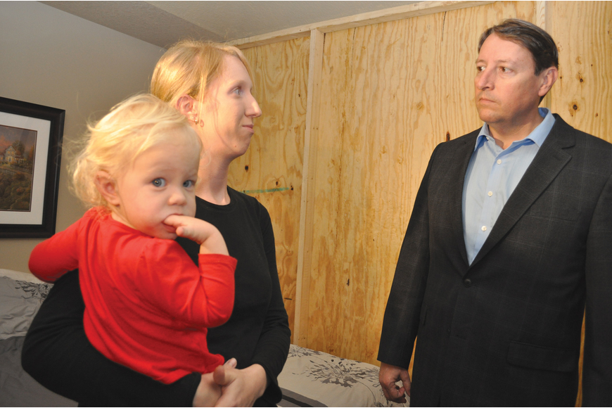 Ashley Delph, holding her daughter, Haley, tells Florida Sen. Bill Galvano about concerns she has with repairs being done on her Willowbrook home.