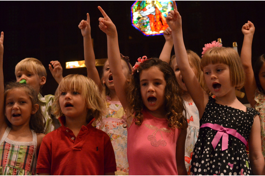 Avery Johanning, Tucker Gravly, Grace Hollingsworth and Noelle Tenaglia sing the Kindergarten Song for parents in the sanctuary.