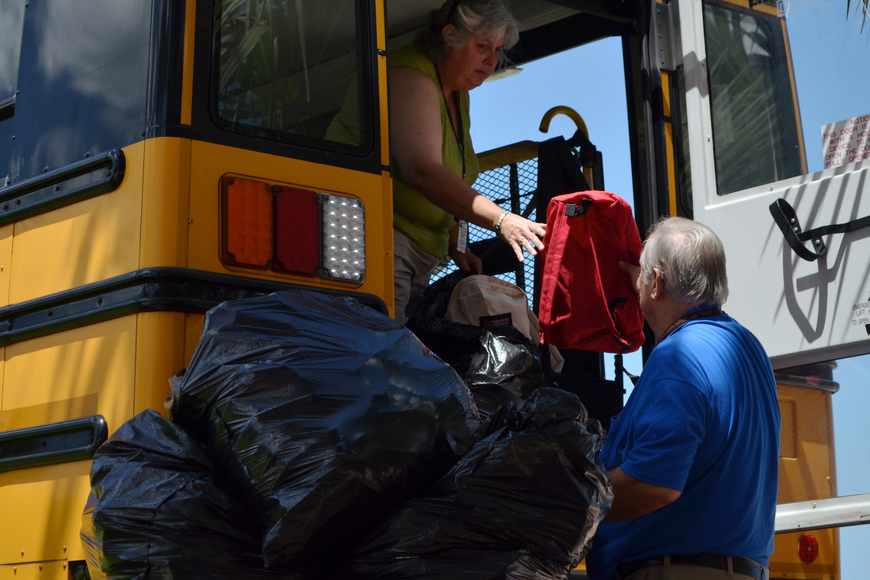Bus drivers Loice Carpenter and Craig Taylor load bags full of backpacks into a school bus.