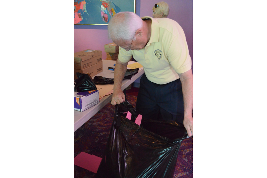 Mike Murphy places the filled backpacks into large bags for delivery.