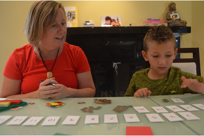 Ian Arov, 5, organizes coins into separate areas depending on their value. He tells kindergarten teacher Shonna Brady the value of each coin.
