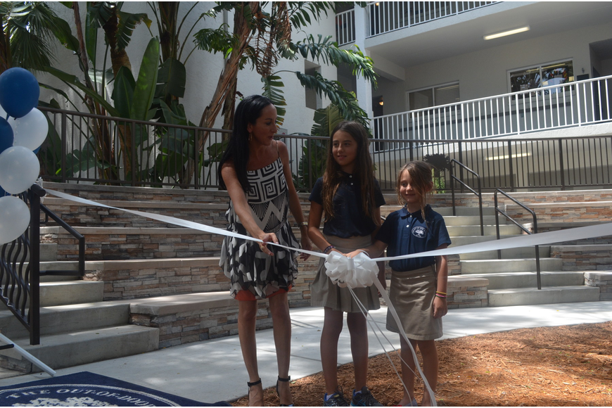 Ashley Kozel and her daughters cut the ribbon at the grand opening of the Kozel Family Amphitheater.