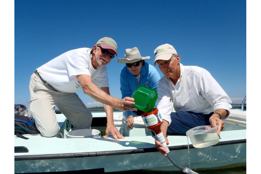 Rusty Chinnis, Caroline McKeon and Manatee County Natural Resources Director Charlie Hunsicker release scallops via a funnel into the bay. (Courtesy Ronda Ryan)