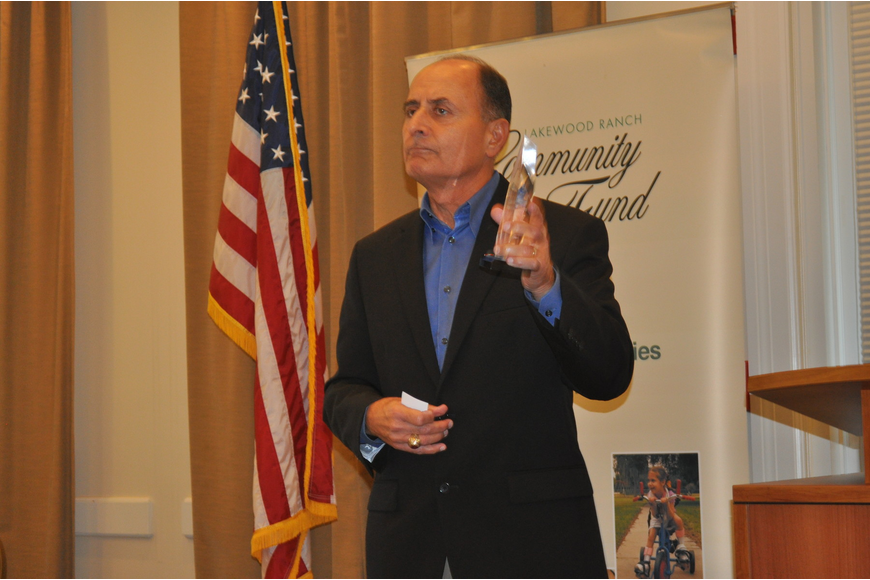 Colonel John W. Saputo, president/owner of Gold Coast Eagle Distributing and former Marine, showed his 2013 C. John A. Clarke Humanitarian Award to the audience.