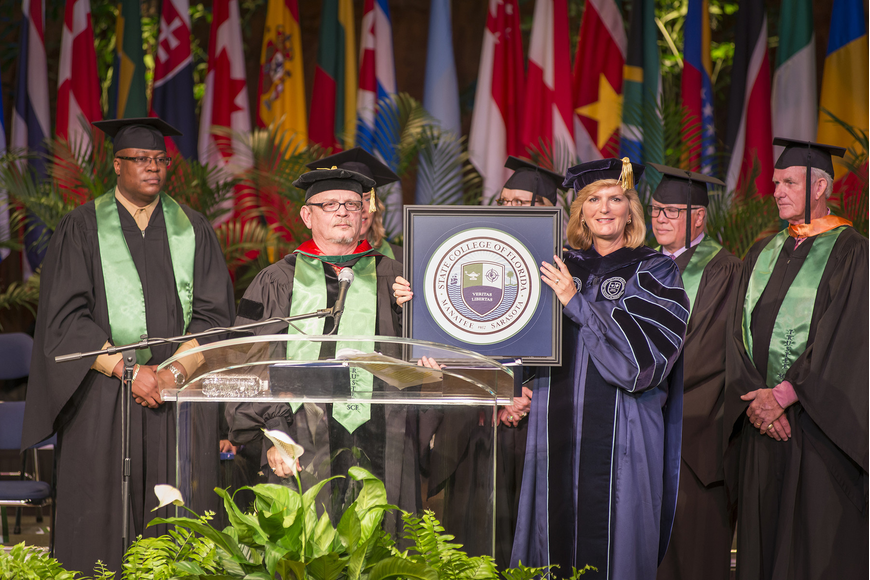 The SCF District Board of Trustees, including Vice Chairman Edward Bailey and Chairman Dr. Craig Trigueiro, present the college seal to President Dr. Carol F. Probstfeld during the inauguration ceremony.