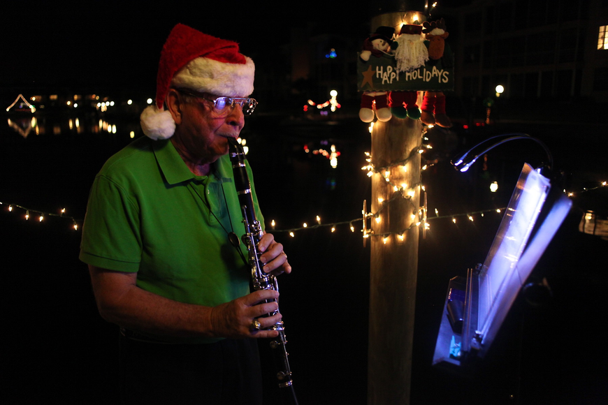 Dockmaster Bob Geraci played Christmas classics on his clarinet as residents walked by his former dock.