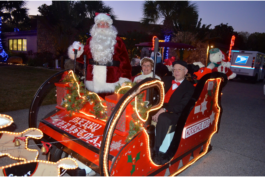 John and Millie Emond, as Mr. and Mrs. Claus, and Bill Crocker play dress up for their neighbors.