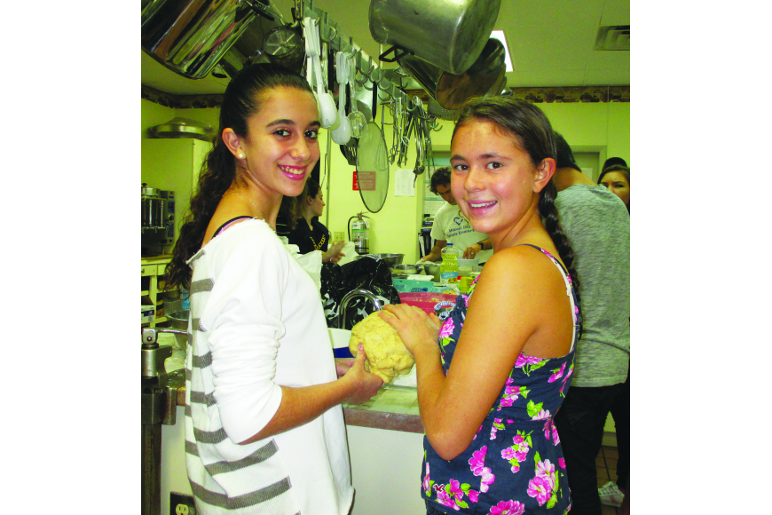 Courtesy from Temple Emanu-El. Allison Kramer and Rachel Towe knead their challah dough.